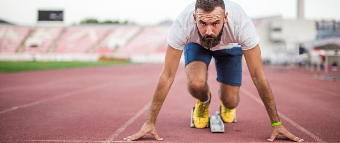 Un homme au départ d'une course sur une piste d'athlétisme