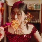 Une femme chinoise en train de manger une pizza avec des baguettes