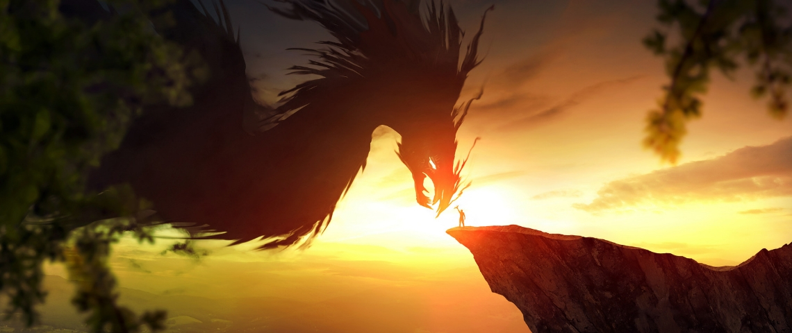 un homme sur un rocher tend la main vers un dragon géant