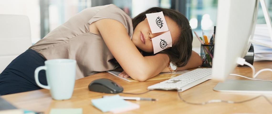 Une femme en train de dormir sur son bureau devant son ordinateur avec des post-it sur les yeux