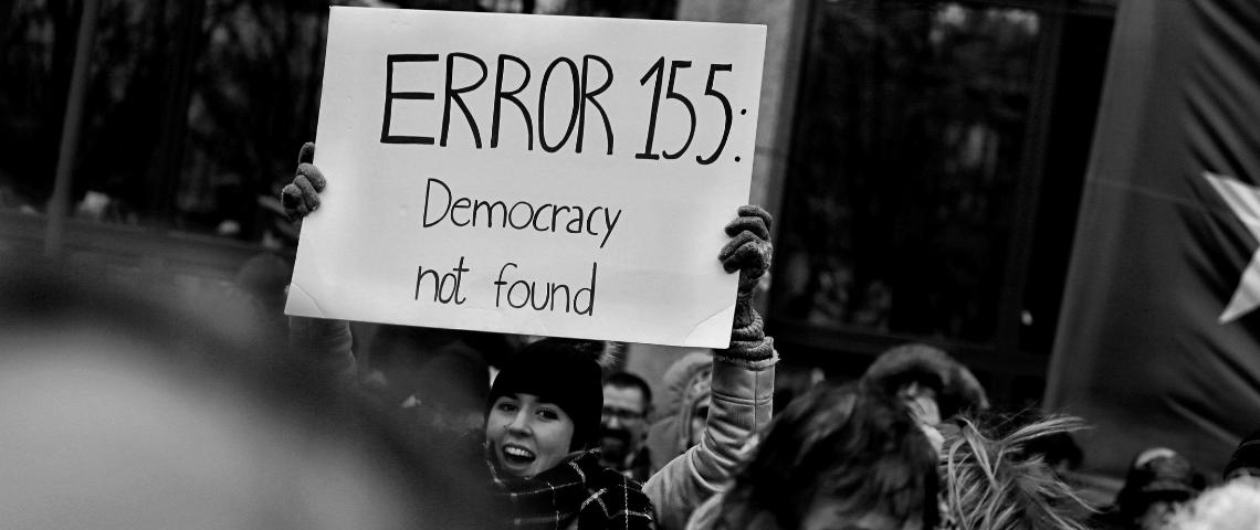 Une femme qui brandit une pancarte Error 155 Democracy not found