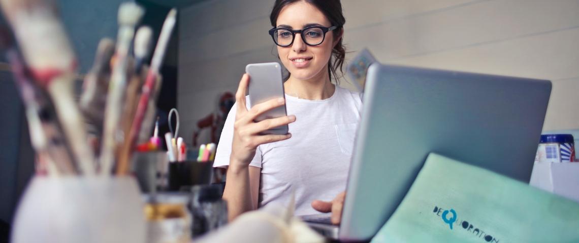 Une femme avec son smartphone devant son ordinateur