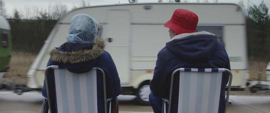 Deux personnes qui regardent une caravane passer