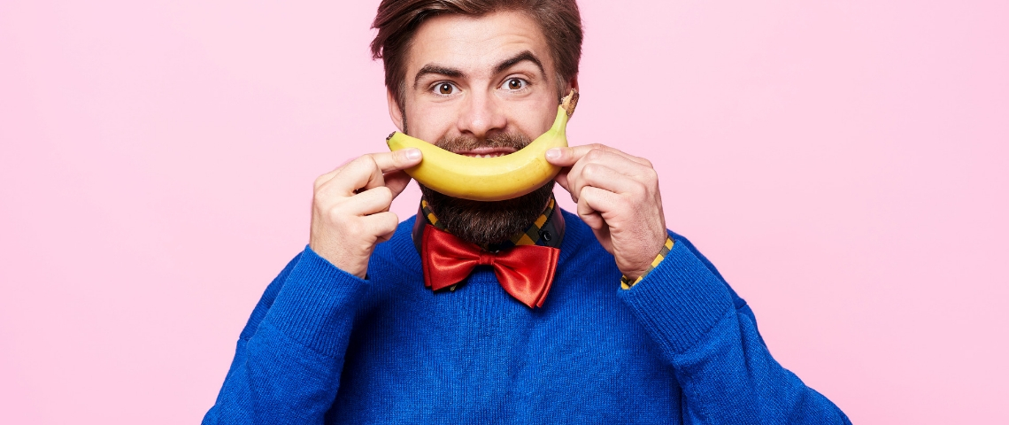 Un homme avec un pull bleu et une banane