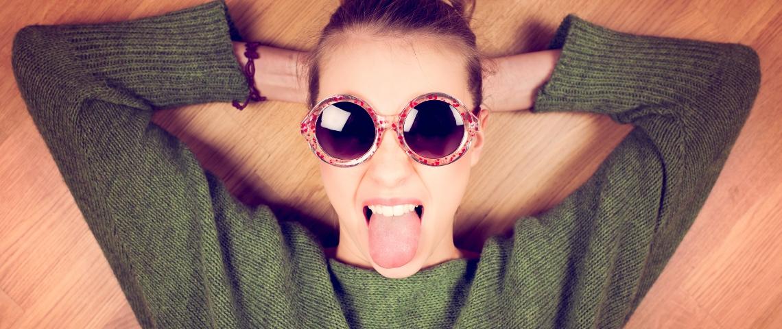 Une femme avec des lunettes de soleil qui tire la langue