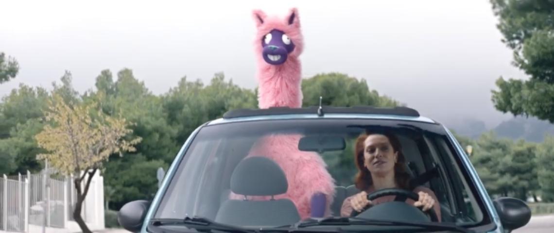 Une femme au volant d'une voiture avec un lama rose