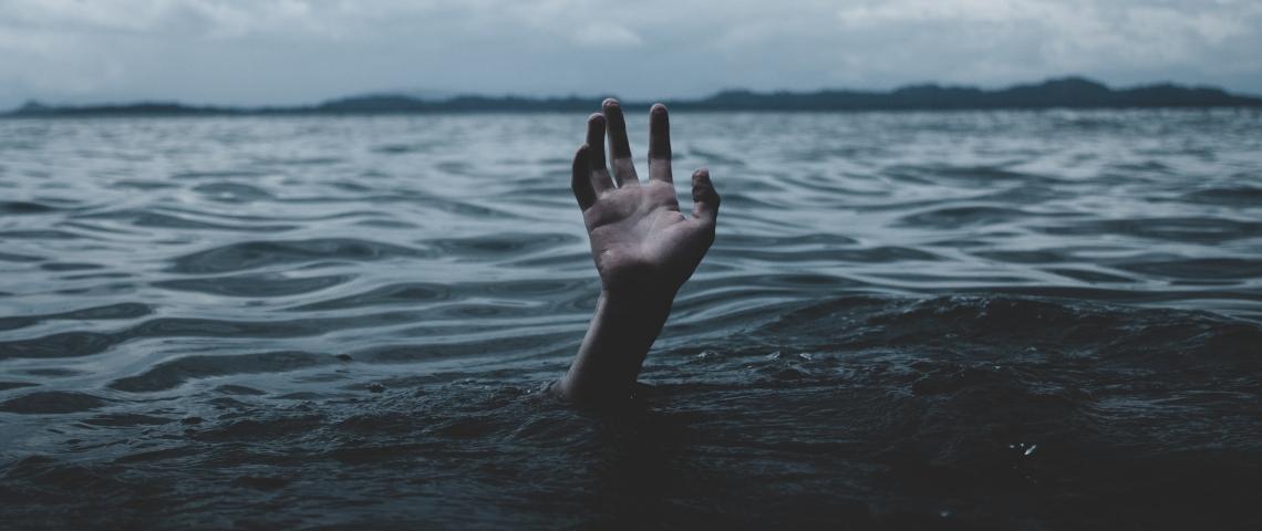 une main essaie de sortir de l'eau, un homme se noie