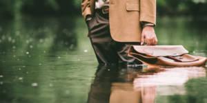 Un homme portant un attaché case avec de l'eau jusqu'aux genoux