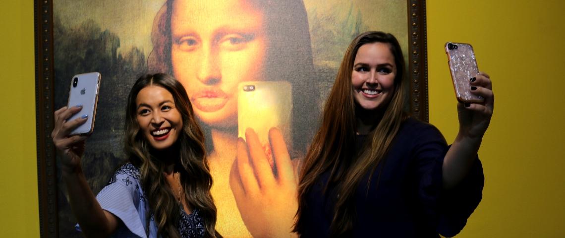 deux filles se prennent en selfie devant la Joconde