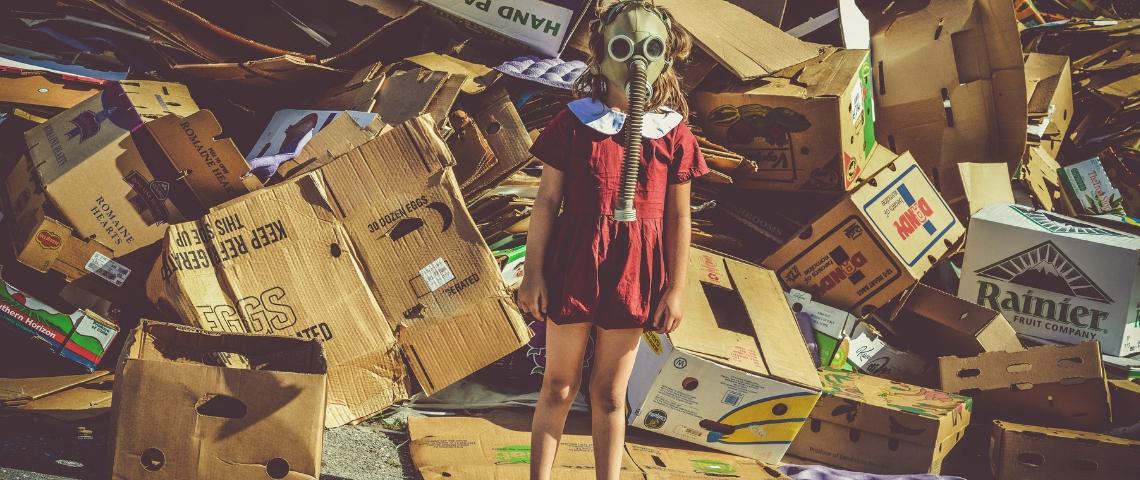 Une petite fille avec un masque à gaz devant un amoncellement de cartons