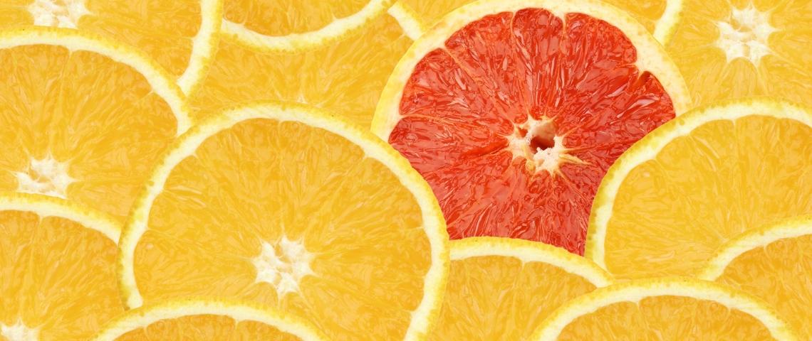 Une orange rouge au milieu de tranches d'oranges