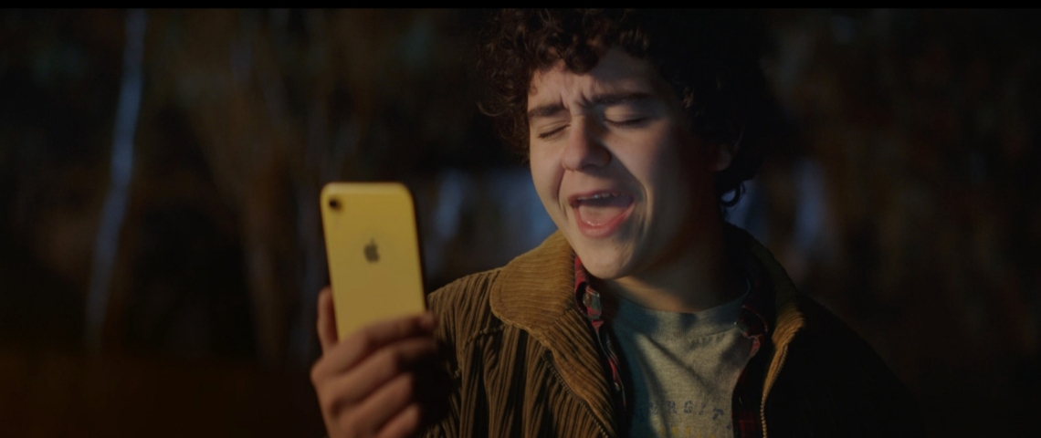 Un garçon qui chante face à son iPhone