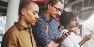 Des gens sur un quai de métro regardent leur portable