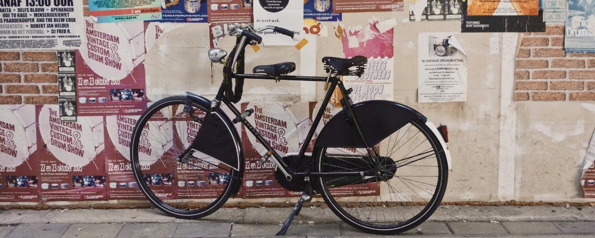 Un vélo noir devant un mur d'affichage