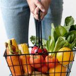 Une personne qui tient un panier de supermarché rempli de fruits et légumes
