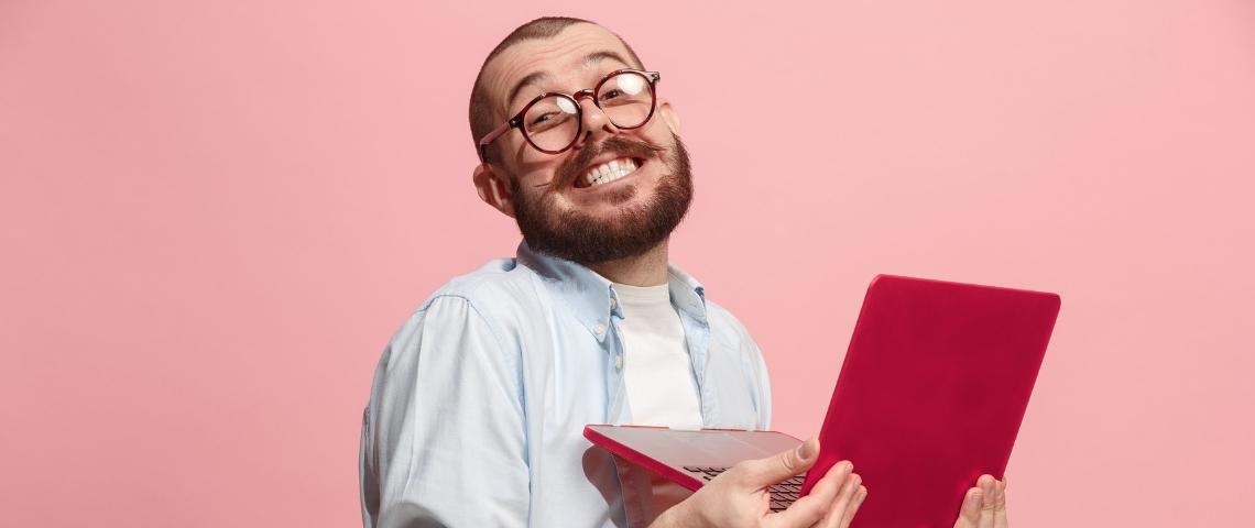 un homme souriant travaille sur son ordinateur rouge