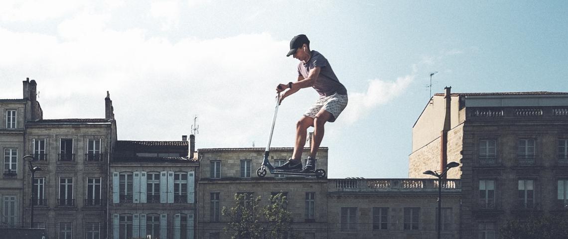 Un homme en trottinette dans les airs