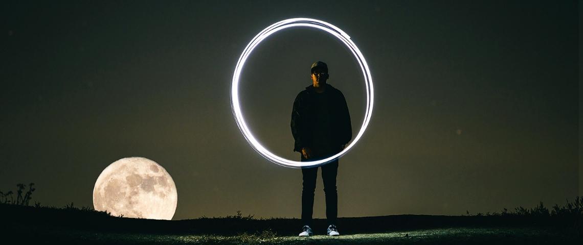 Un homme, la lune et un cercle lumineux