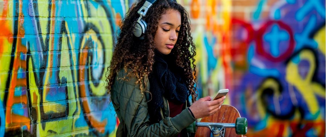 Une adolescente avec un casque sur les oreilles qui regarde son téléphone