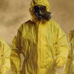 Trois exterminateurs dans des combinaisons jaunes, avec de la fumée