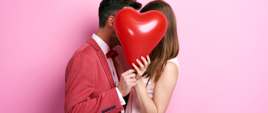Un couple derrière un ballon rouge en forme de coeur