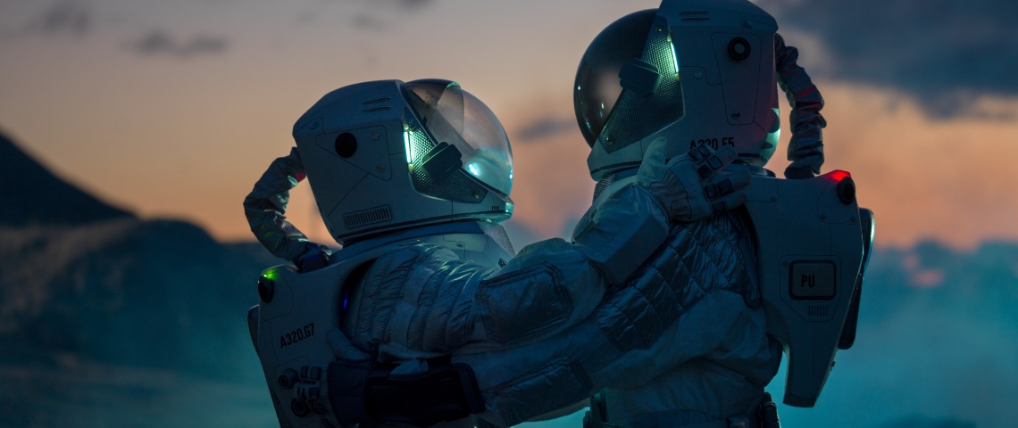 Deux personnes en combinaison d'astronaute qui se font un câlin