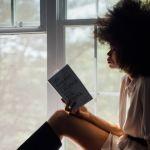Une femme noire lit à côté de sa fenêtre