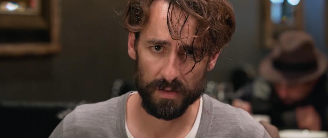 Un homme avec une barba qui regarde la caméra