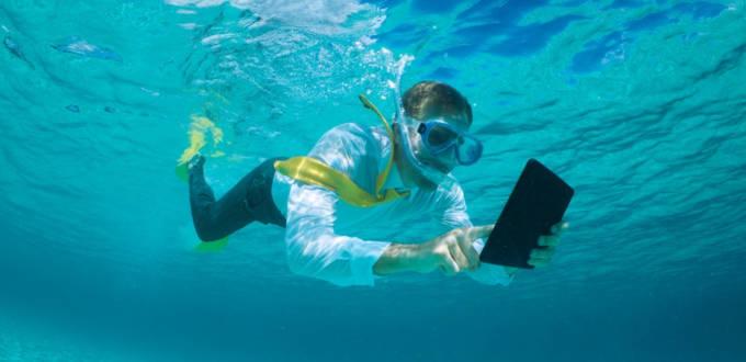 Un homme d'affaire regarde une tablette dans une piscine