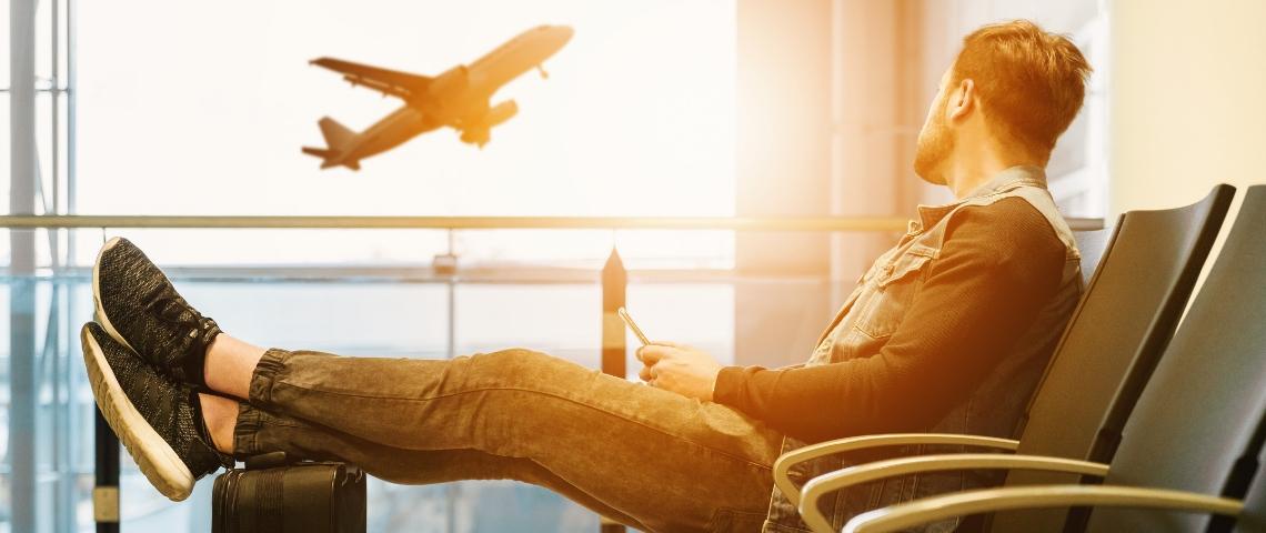 un homme regarde un avion s'envoler dans un aéroport