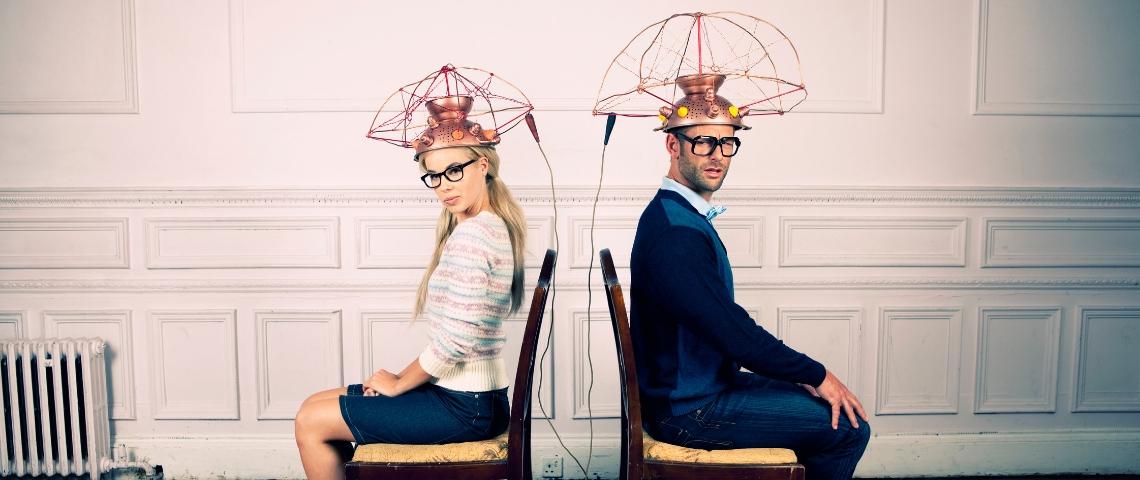 Un homme et une femme dos à dos assis sur une chaise avec un casque sur la tête
