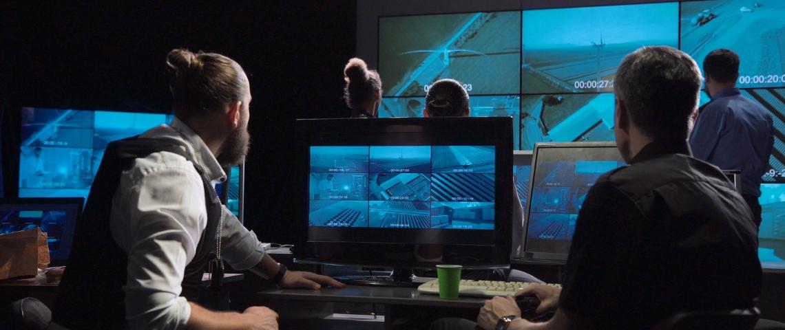 Des hommes dans une piece sombre qui regardent des écrans