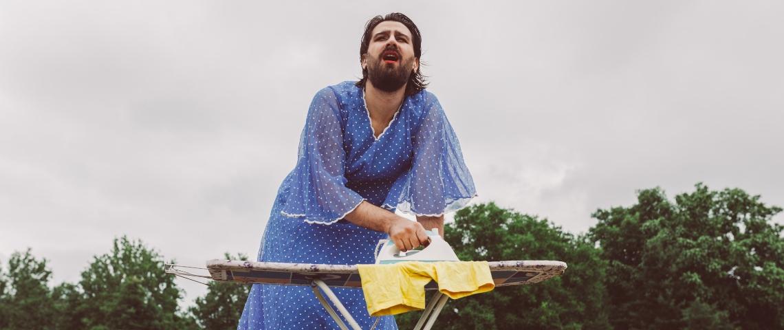 Un homme travesti repasse ses vêtements