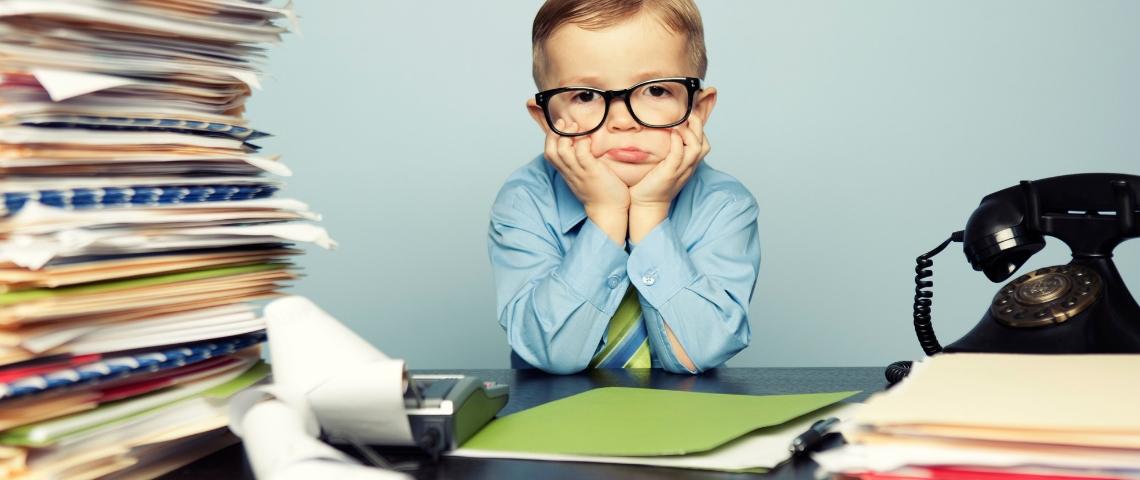 Un enfant avec des lunettes assis à un bureau avec une pile de dossiers