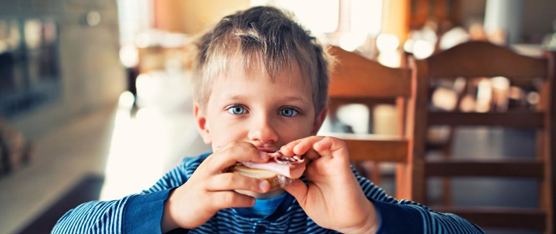 un jeune garçon mange un sandwich au jambon