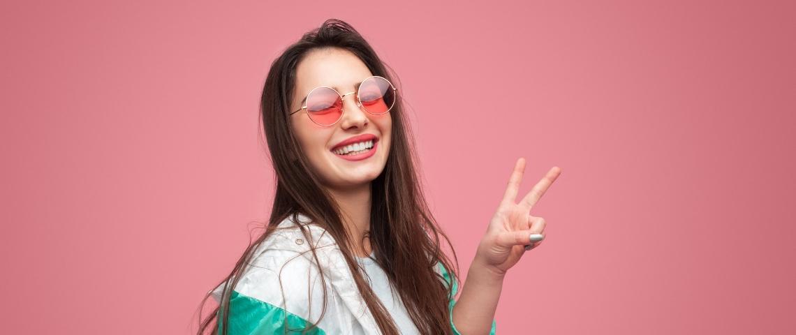 Une jeune femme sur fond rose en lunettes rose fait un signe peace des doigts