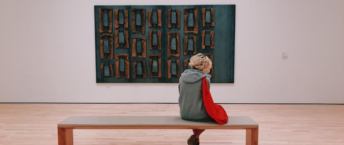 une jeune femme au musée assise devant un tableau