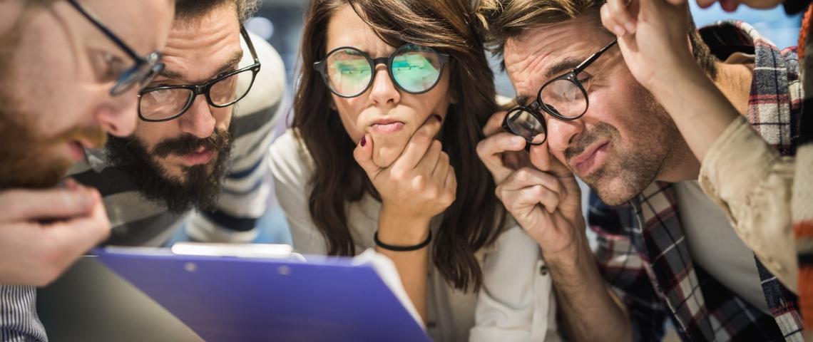 Un groupe de jeunes employés dubitatifs face à un document mystère