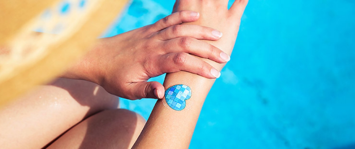 Une femme en train de s'appliquer de la crème solaire au-dessus d'une piscine