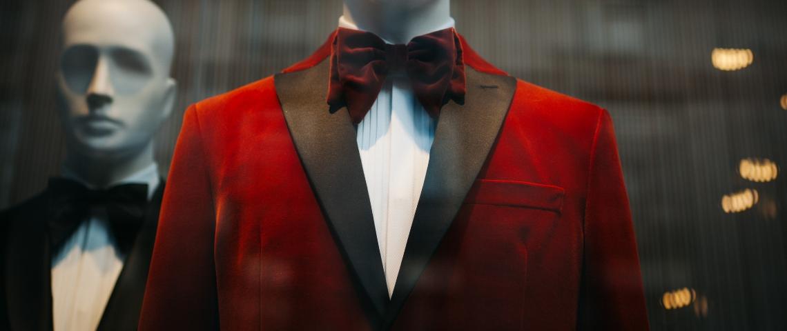 Un mannequin vêtu d'un costume rouge et d'un noeud papillon