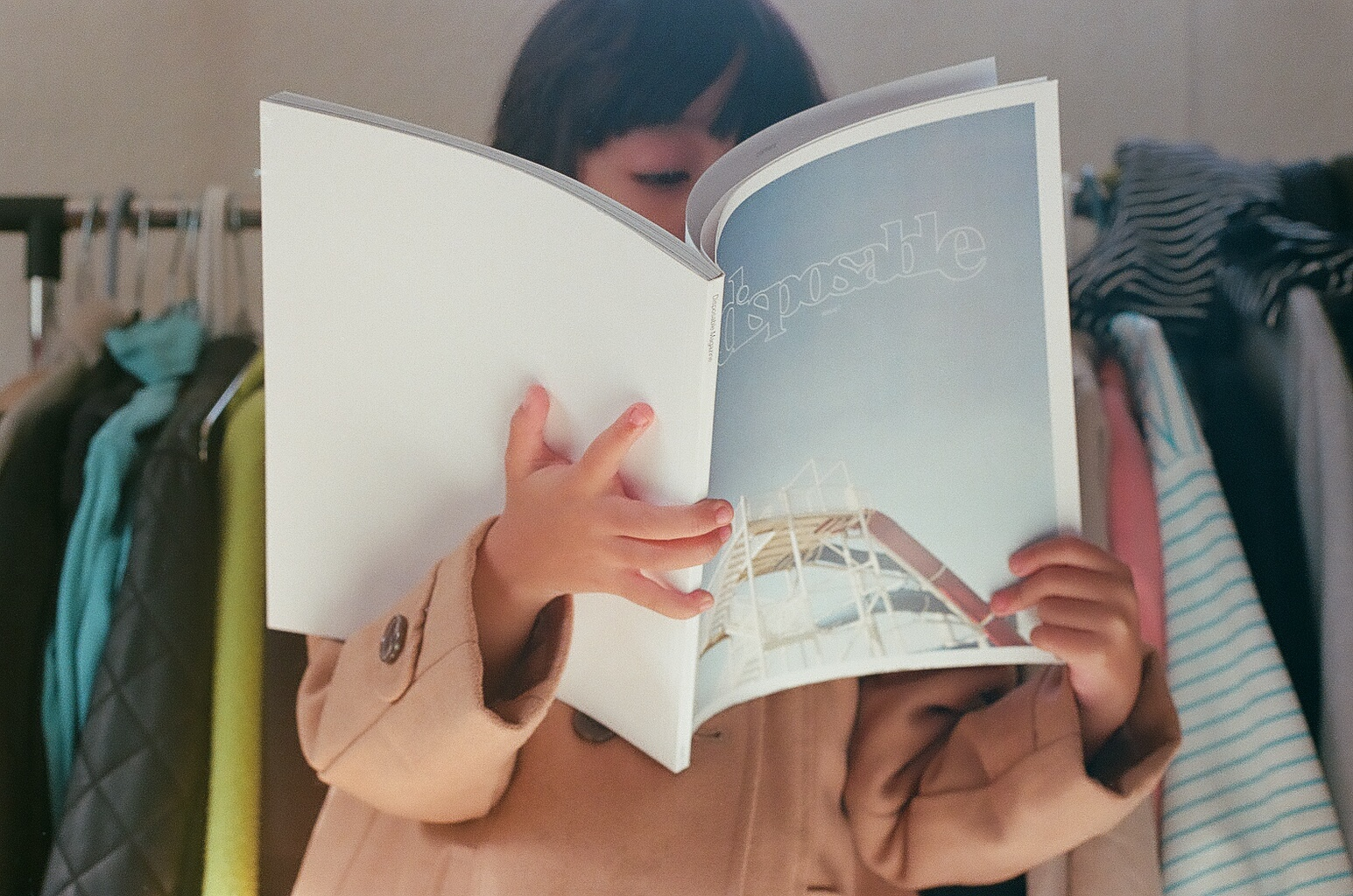 une fille lisant, cachée, par un magazine