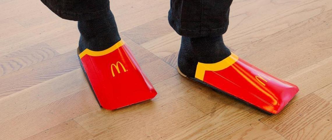 Des pieds avec des emballages de frites McDonald's en guise de chaussures