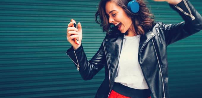 Une femme qui danse avec un casque audio bleu sur les oreilles