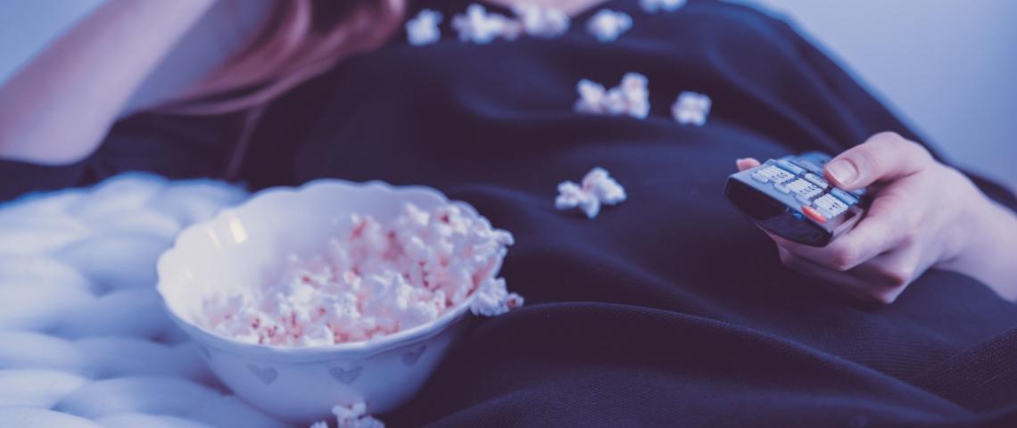 Une femme qui regarde la télé en mangeant du popcorn