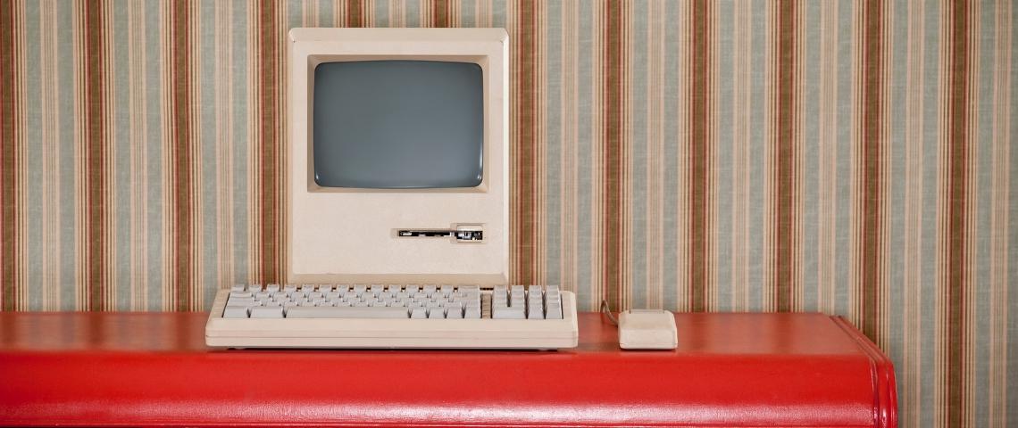 Un ordinateur rétro sur un bureau rouge