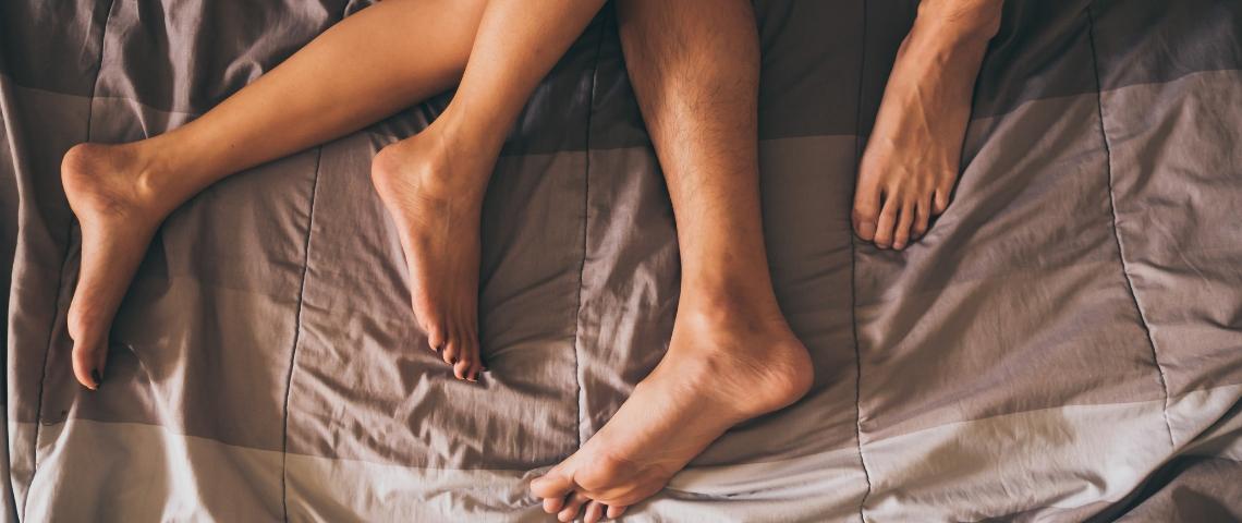 Les pieds d'un couple dans un lit