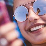 Une jeune femme à lunettes écoute son téléphone avec un casque