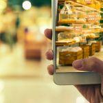 Une femme en train de faire ses courses avec son smartphone pour avoir des offres grâce à la réalité augmentée