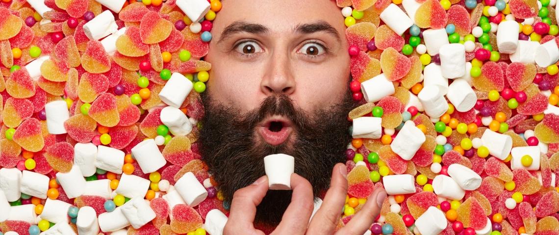un homme barbu sur fond de bonbons
