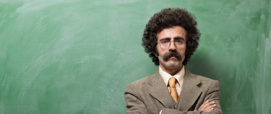 Un instituteur devant un tableau de salle de classe ardoise